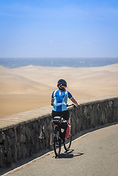 Rear view of woman cycling on road by sand dune and sea