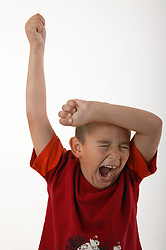 Young boy flinging his arms in the air and screaming,