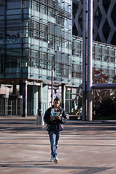 © Licensed to London News Pictures . 24/09/2014 . Media City , Salford , UK . Autumn sunshine and big reflected light off the surface of glass buildings at Salford's Media City this morning as commuters travel to work  . Photo credit : Joel Goodman/LNP