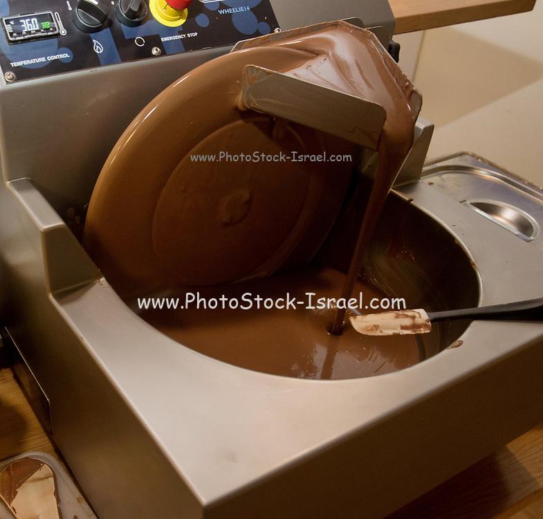 Mixing and blending Dark chocolate by an artisanal chocolatier