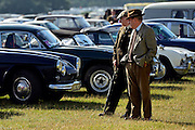 © Licensed to London News Pictures. 15/09/2013. Chichester, UK Men look at period cars in the carpark. People enjoy the atmosphere at the last day of 2013 Goodwood Revival. The event recreates the glorious days of motor racing and participants are encouraged to dress in period dress. The revival is the only event of its kind to be staged entirely in the nostalgic time capsule of the 1940s, 50s and 60s Photo credit : Stephen Simpson/LNP.