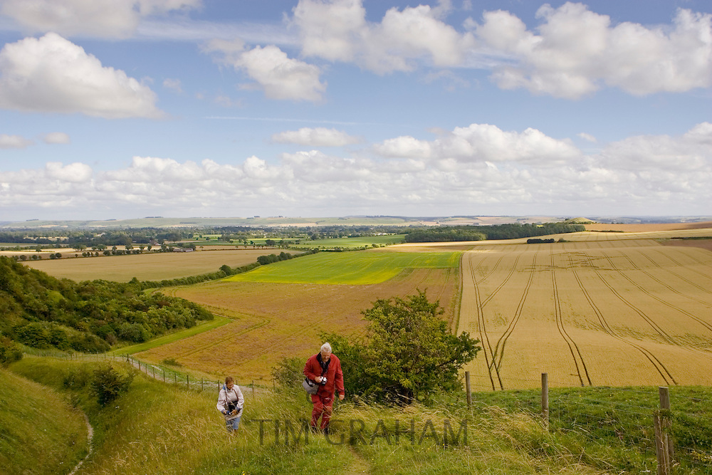 Ramblers walk the footpath overlooking a crop circle in Vale of Pewsey, Wiltshire, England, United Kingdom