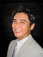 Asian man, smiling in grey suit and tie in front of black background