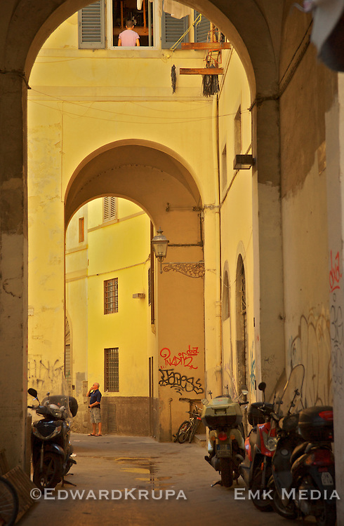 A man on a cellphone in an alleyway in Florence.