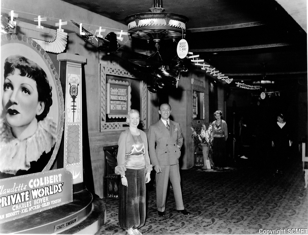 1935 Theater manager and usher greet theatergoers inside lobby of Grauman's Egyptian Theater