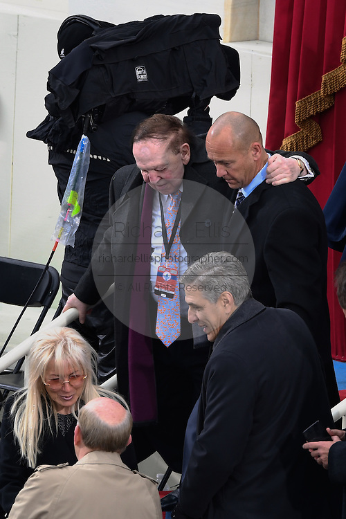 American casino magnate Sheldon Adelson is helped down the stairs as he arrives with his wife Miriam Ochsorn for the Inauguration of President-elect Donald Trump as the 45th President on Capitol Hill January 20, 2017 in Washington, DC.