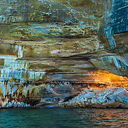 A natural arch in the rocky shore of Pictured Rocks National Lakeshore, Michigan. Viewed at sunset from a boat on Lake Michigan.