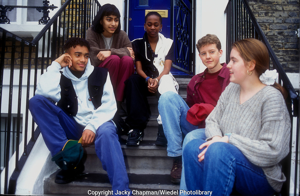 Group of teenaged friends meeting up on the front step.