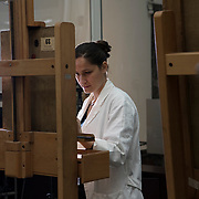 Milan, Italy, 11 June 2019. Transparent restoration workshop inside the Pinacoteca di Brera. Sofia Incarbone, restorer of the Pinacoteca, engaged in the cleaning test of the painting Madonna with child by Marco dʻOggiono.<br />