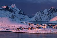 Pink winter light at dawn shines over small coastal village and mountains, Reine, Moskenesøy, Lofoten Islands, Norway
