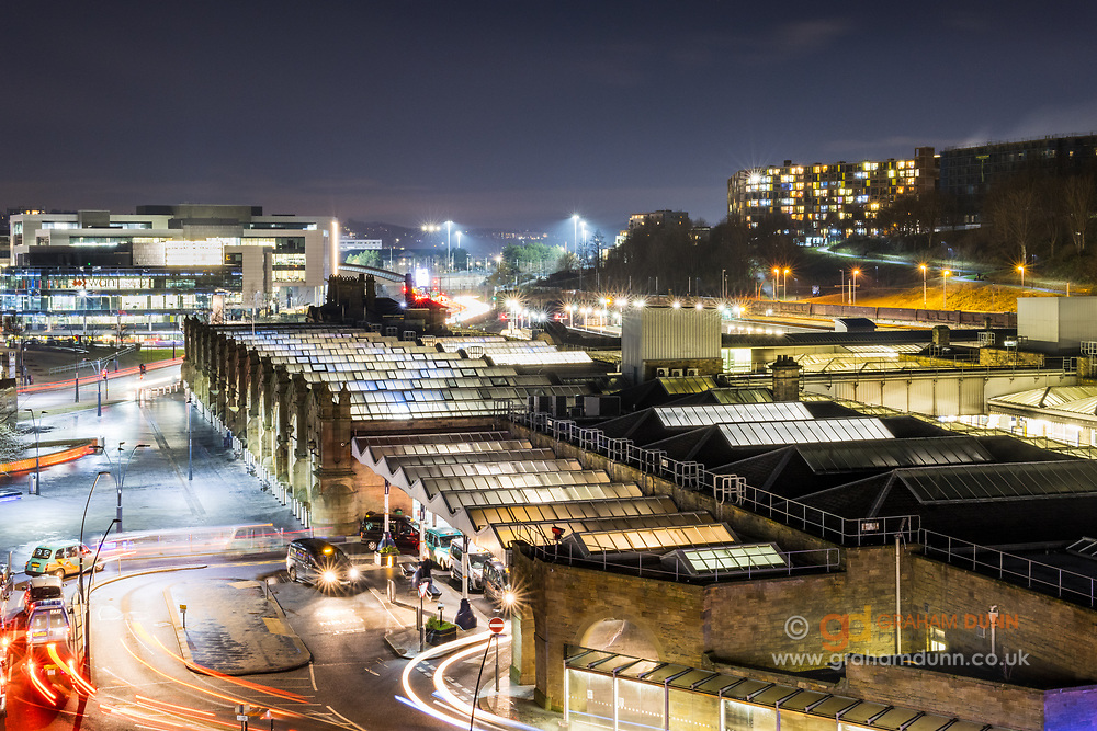 Traffic flows in and out of Sheffield's Railway Station. Low light levels at dusk allow for long exposures and the capture of light trails as vehicles pass through the scene. An elevated viewpoint gives sight of Sheaf Street, the Parkhill Flats and beyond. An urban cityscape / landscape scene in South Yorkshire, England, UK.
