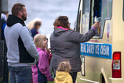© Licensed to London News Pictures.16/08/2020 Edinburgh,UK. Members of the public are seen buying ice-cream on Sunday noon at Portobello Beach in Edinburgh, Scotland. Weather forecast for Edinburgh say maximum temperatures reach 15 degrees. Concerns are growing over the potential of widespread job losses in Edinburgh tourism industry two-thirds of the city's hotels rooms may be left lying empty this month. Photo credit: Marcin Nowak/LNP