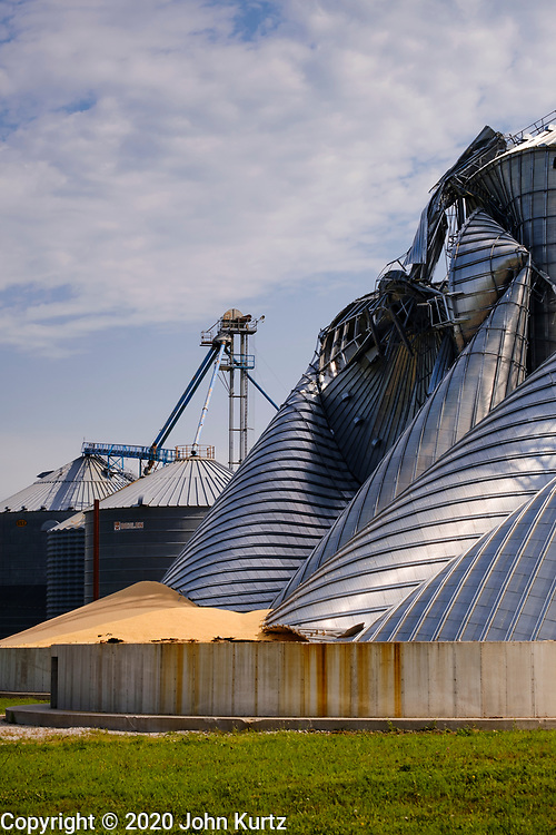 """12 AUGUST 2020 - MADRID, IOWA: Grain silos at the Heartland Cooperative in Luther were destroyed during the storm Monday. According to Iowa Governor Kim Reynolds, the storm damaged 10 million acres of corn and soybeans in Iowa, about 1 one-third of Iowa's 32 million acres of agricultural land. Justin Glisan, Iowa's state meteorologist, said the storm Monday, Aug. 10, lasted 14 hours and traveled 770 miles through the Midwest before losing strength in Ohio. The storm was a seldom seen """"derecho"""" that packed straight line winds of nearly 100MPH. The storm pummelled Midwestern states from Nebraska to Ohio.    PHOTO BY JACK KURTZ"""