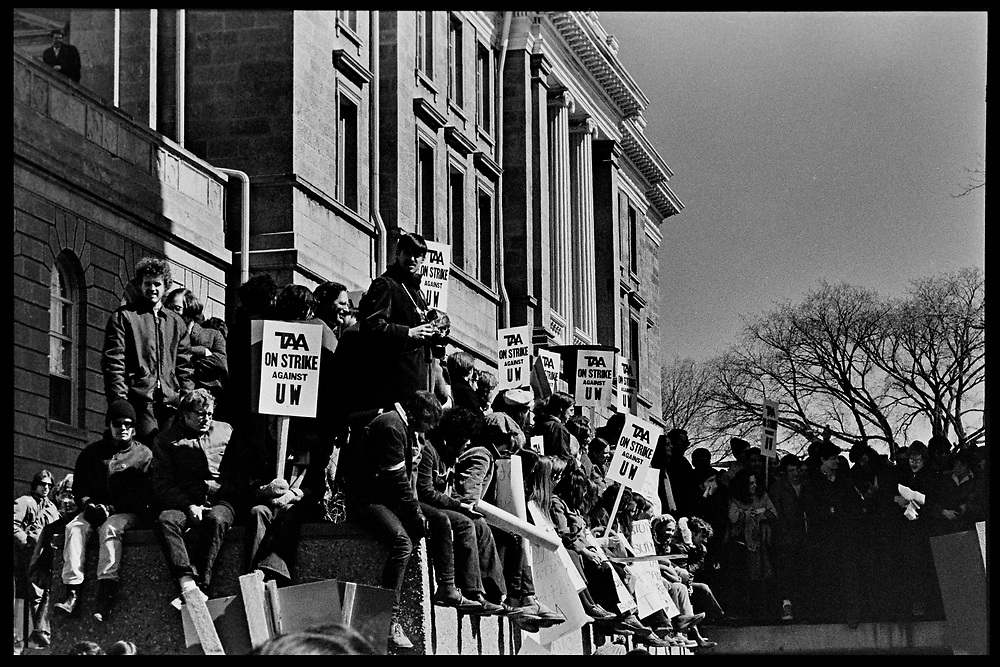 Madison, WI - March 1970. On March 15, 1970, the University of Wisconsin - Madison Teaching Assistants' Association voted to strike, and the campus was filled with picket lines as well as demonstrations of related and other issues. The strike lasted until early April, when the Association and University came to an agreement. Crowds with picket signs gather on campus.