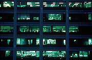 Building exterior of office windows lit at night. New York NY. ( The New York City Office of Collective Bargaining ) Manhattan Downtown