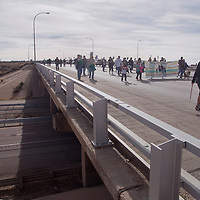 A group of about 50 people cross Miyamura bridge as they marched from the cultural center to Larry Brian Mitchell Recreation Center Monday for Martin Luther King Day.