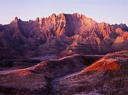 Salmon colored light of sunrise illuminating the Badlands, Badlands National Park, South Dakota.