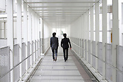 two young business executives walking down a corridor