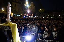 """People praying with candles on the place saint michel in front of a statue of Virgin Mary during an evening of prayer and songs organized by Catholics community the day after Notre Dame Cathedral blaze with a march organized from Saint-Sulpice church to Saint Michel and finally next to Notre Dame Cathedral in Paris early on April 16 the day after the beginning of the fire , 2019. A huge fire that devastated Notre-Dame Cathedral is """"under control"""", the Paris fire brigade said early on April 16 after firefighters spent hours battling the flames. Photo by Raphael Lafargue/ABACAPRESS.COM"""