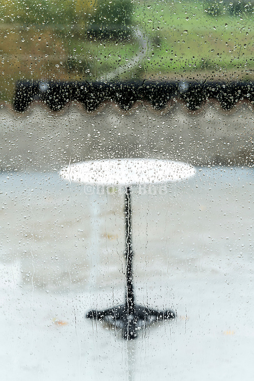 round bistro table outside in the rain seen trough a window with water drops