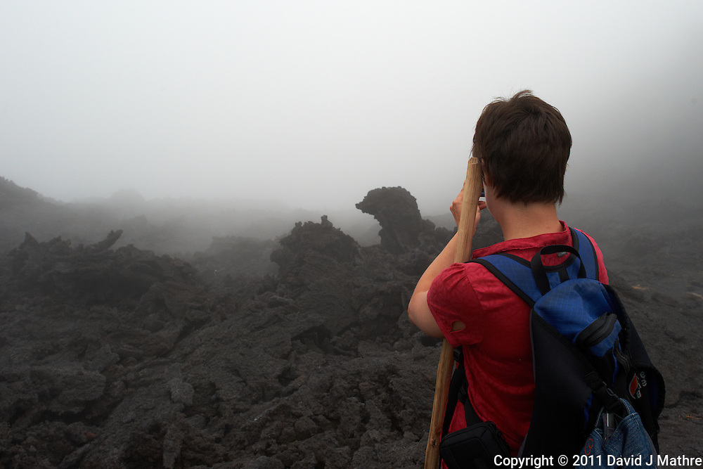 Hiker taking an image of the lava in the mist. On the trail to the Volcano. Pacaya Volcano National Park. Image taken with a Nikon D3x and 24 mm f/1.4G lens (ISO 320, 24 mm, f/8, 1/320 sec). Raw image processed with Capture One Pro and Photoshop CS5.