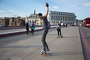Skateboarders skating across Blackfriars Bridge. One is performing a trick whilst filming himself with a camera. London, UK.