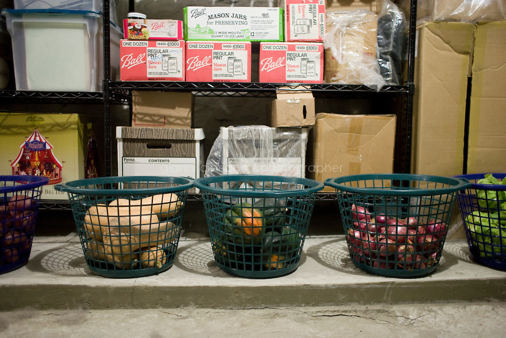 30 October, 2008. New York, NY. (L-R) Potatoes, butternut squashes, acorn squashes, onions and cabbages are momentarily stored in baskets in the ground floor of Cindy Worley's Harlem brownstone, waiting for her to finish setting up the root cellar.Cindy Worley is setting up a root cellar in her Harlem brownstone. They would normally be store in sand or wooden cases. Cindy Worley grew up using root cellars and she now preserves fresh food produced either at the Joseph Daniel Wilson Memorial Garden in Harlem, or at the Community Supported Agriculture (CSA) farm in Upstate New York, which she is member of. The food she store is both consumed by her and her husband, and sold to support the Kitchen, a service provided by the Food Bank for New York City.   ©2008 Gianni Cipriano for The New York Times<br /> cell. +1 646 465 2168 (USA)<br /> cell. +1 328 567 7923 (Italy)<br /> gianni@giannicipriano.com<br /> www.giannicipriano.com