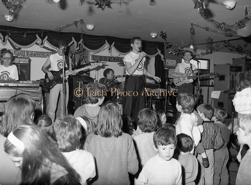 Christmas Party With Johnny Logan..1986..16.12.1986..12.16.1986..16th December 1986..At the 'Embankment',Tallaght, a charity Christmas Party was held for deprived children of the area. The main attraction was the singer and entertainer Johnny Logan,who with his band,entertained the children. Santa Claus took time off from his busy schedule to give a present to all the boys and girls. A great time was had by all...Image shows Johnny encouraging the children to join in, in the singing