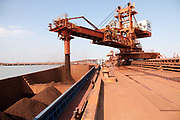 A conveyer belts loads up a barge at an iron-ore transfer and storage center operated by the Shanghai International Port Group in Shanghai, China on 26 January 2010. China's economic boom and hunger for natural resources has been a blessing for countries such as Australia and Brazil, who controls most the world's high quality iron ore deposits.
