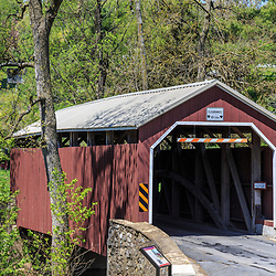 Leola, PA, USA - April 26, 2016: Zook's Mill Covered Bridge, which spans the Cocalico Creek in Lancaster County, PA, is 74 feet long and painted traditional red.