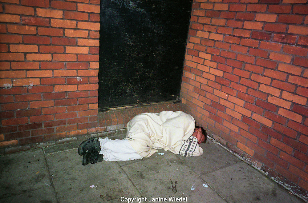 Homeless person sleeping rough on the pavement in London.
