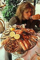 woman eating seafood from a Plateau Fruits de Mer, in France - photograph by Owen Franken