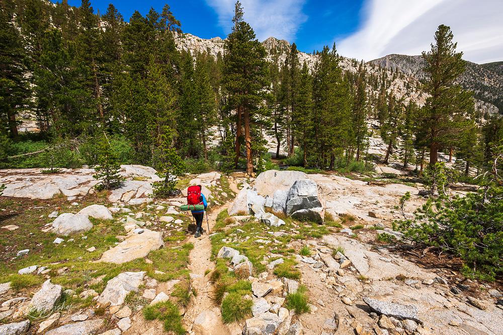 Backpacker on the Treasure Lakes trail above South Lake, John Muir Wilderness, Sierra Nevada Mountains, California USA