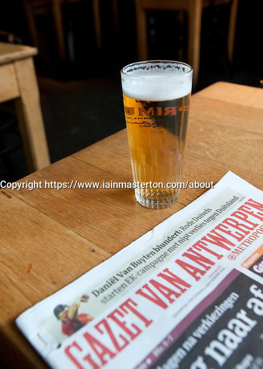 Belgian beer and newspaper in typical cafe in Antwerp Belgium