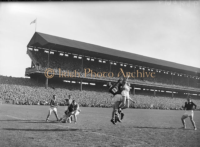 Galway goalie Farrell jumps to clear from Kerry forwards the All Ireland Senior Gaelic Football Championship Final, Kerry vs Galway in Croke Park on the 27th September 1959. Kerry 3-7 Galway 1-4.