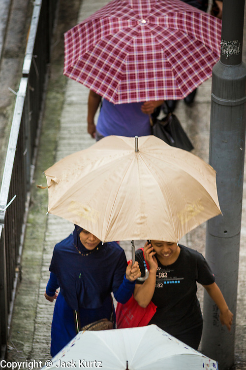 13 AUGUST 2013 - HONG KONG: People near Cochrane Street in Hong Kong use umbrellas to protect themselves from the rains of Typhoon Utor. Typhoon Utor (known in the Philippines as Typhoon Labuyo) is an active tropical cyclone located over the South China Sea. The eleventh named storm and second typhoon of the 2013 typhoon season, Utor formed from a tropical depression on August 8. The depression was upgraded to Tropical Storm Utor the following day, and to typhoon intensity just a few hours afterwards. The Philippines, which bore the brunt of the storm, reported 1 dead in a mudslide and 23 fishermen missing at sea. The storm brushed by Hong Kong bringing several millimeters of rain and moderate winds to the island but causing no reported damage or injuries. It is expected to make landfall in China.   PHOTO BY JACK KURTZ