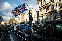 © Licensed to London News Pictures. 10/02/2016. London, UK. A black cab driver stands on his bonnet waving the union flag  as thousands of London black cab drivers stage a protest in Westminster, London against Government interference in the taxi industry and 'active support' for Uber, which they allege is a 'tax avoiding global corporation' Photo credit: Ben Cawthra/LNP