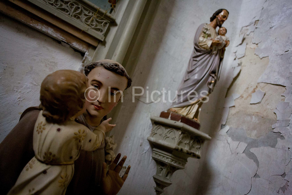 Plaster Catholic idols in a corner of the Saint-Gervais-Saint-Protais church at Le Grand-Pressigny, Indre-et-Loire, France. In the foreground is a small child in the arms of a monk with other figurines in the background. <br /> The Gothic style church has its origins in the 12th century but has been added to and amended over the centuries like so many other ancient places of worship here in the Loire Valley and the rest of the country.
