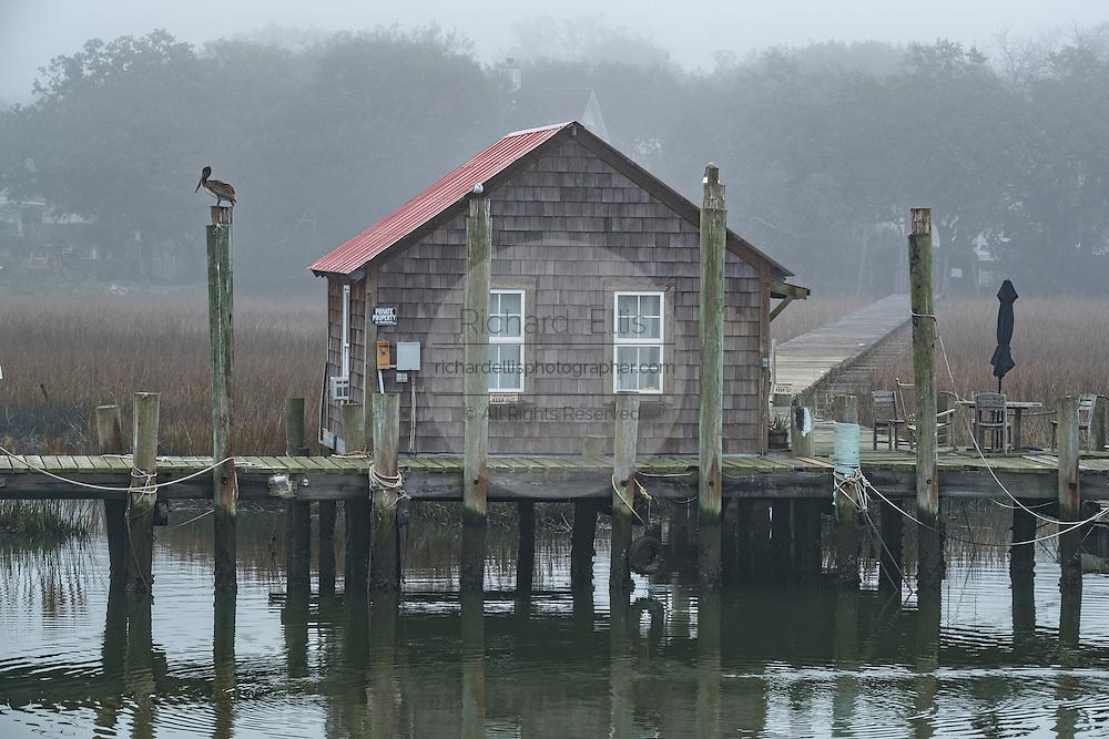 Old shingle sided boat house along Shem Creek on a foggy winter morning in Charleston, South Carolina.