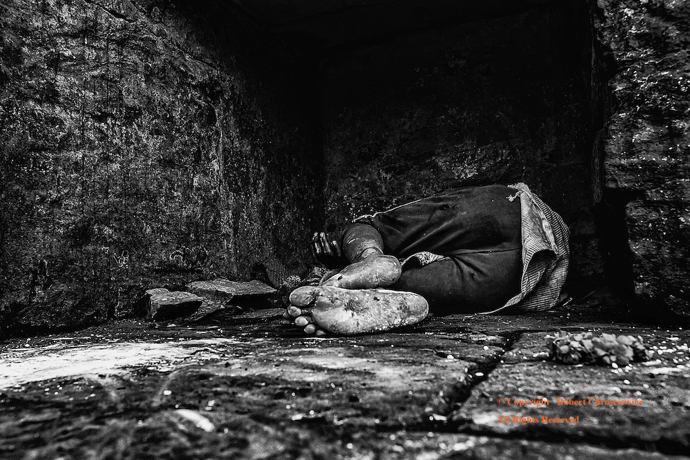 Alone at Last (B&W): A young homeless boy lies dead-asleep in an obscure, crypt like recess, underneath several feet of stone and the busy Dashaswamedh Ghat, near the river-side cremation Ghats, Varanasi India.