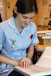 Student Nurse reading up on nursing procedures,