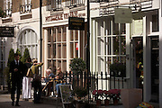 A young man in a dark suit walks past chatting friends who sit in spring sunshine outside their French-styled cafe Valerie on Motcomb Street.  Belgravia's Motcomb Street SW1, was first shown on a London map in 1830. by 1854 it was populated by buisinesses such as 'cowkeepers', bakers and grocers. Today there is a mix of upper-class businesses like as Patisserie Valerie, Errol Douglas the exclusive hairdressers, Stewart Parvin the royal couturier and Moyses Stevens the florist whose floral displays are seen on their window ledge and next to ornate pavement railings outside.