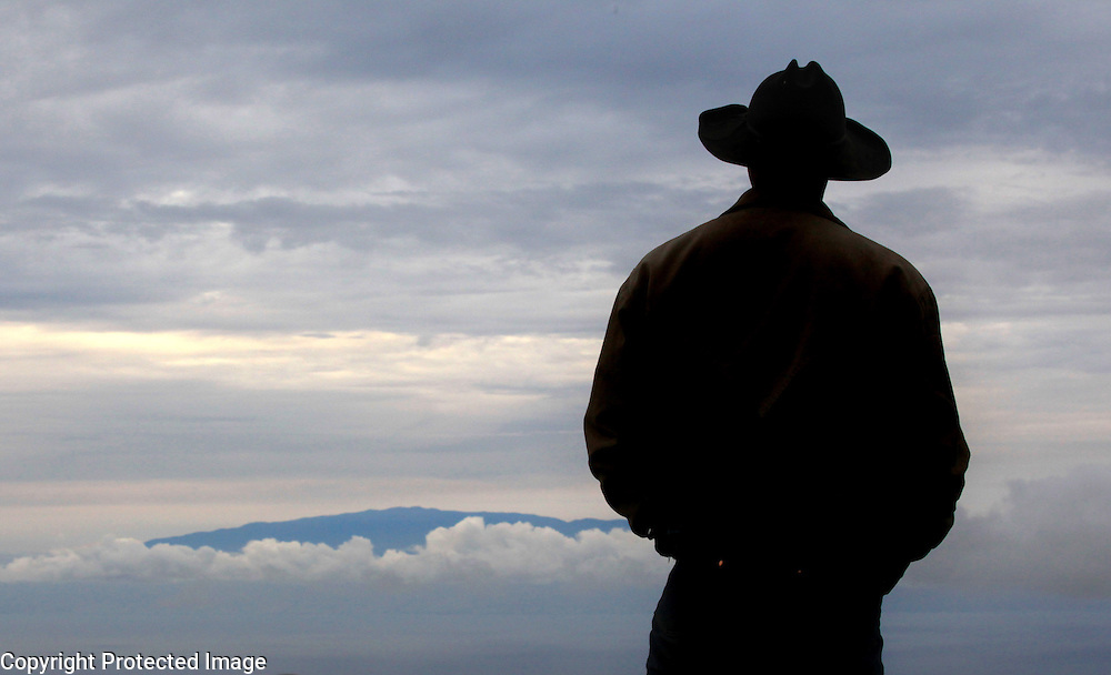 """Hawaiian cowboy, Wayne Tachera, stands at the top of Kahua Ranch, where he works and looks over the beautiful landscape after a hard day's work in North Kohala, Hawaii. Tachera lives with his two daughters, Kamehana, 10, and Nahe, 8, in """"cowboy housing"""" which is subsidized by the ranch as part of a cowboy's benefit package. """"We get free housing, free electricity, free water.  It makes up for cowboy pay because cowboy pay is not much at all"""","""" says Tachera. """"Sometimes we go to the mountain up there and you can see the whole entire ridge and beaches and stuff like that,"""" says Tachera's older daughter, Kamehana, 10."""