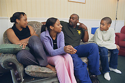 Father sitting on sofa in living room with teenage son and daughters,
