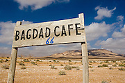 """A wooden sign reading """"Bagdad Cafe"""" indicates the name of a cafe on the road from Damascus to Palmira, in them iddle of the dessert, in Syria."""