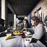 Nederland, Amsterdam , 4 december 2012..de gekraakte Sint Jozefkerk in Bos en Lommer..waar zo'n tachtig asielzoekers sinds zondag worden opgevangen. Ze bivakkeerden eerder in een tentenkamp in Osdorp..vooral jongeren springen voor deze vluchtelingen in de bres, maar ook allochtone buurtbewoners van zowel Marokkaanse als Turkse afkomst komen met pannen couscous  rijst en soep om de hongerige asielzoekers te voeden. Er is weinig electriciteit momenteel in de kerk en het is er koud..Op de foto: jonge vrijwilligers en asielzoekers tijdens het avondmaal..VOORKEURFOTO!.Foto:Jean-Pierre Jans
