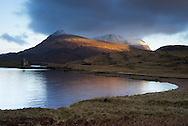 Ardvreck Castle on Loch Assynt, Scotland, as dawn light clears away storm clouds. Photograhy copyright Andrew Tobin/tobinators.com