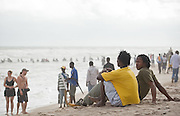 Young men sit on the sand at Labadi Beach in Accra, Ghana on Sunday October 8, 2007. Also known as La Pleasure Beach, it is one of the city's most popular hangouts, especially on Sunday afternoons.