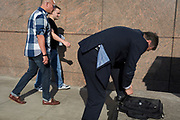 A commuter pauses to tie a shoelace on London Bridge, the oldest of the capital's crossing over the river Thames between the capital's financial district, the City of London, and Southwark on the south bank, on 15th May 2018, in London, UK.