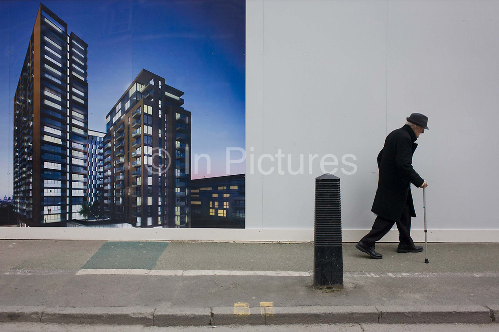 An elderly man walks bent past a regeneration project hoarding image at Elephant & Castle, London borough of Southwark. The older generation sees their neighbourhood renew, they have to live among disruption and change. Southwark Council's development partner, Lend Lease is regenerating over 28 acres across three sites at the heart of Elephant & Castle, in what is the last major regeneration opportunity in zone 1 London. The vision for the £1.5 billion regeneration is to build on the area's strengths and vibrant character in order to re-establish Elephant & Castle as one of London's most flourishing urban quarters. The Elephant & Castle regeneration is of a scale rarely seen in central London and includes almost 3,000 new homes, plus office, retail, community, leisure and restaurant space.